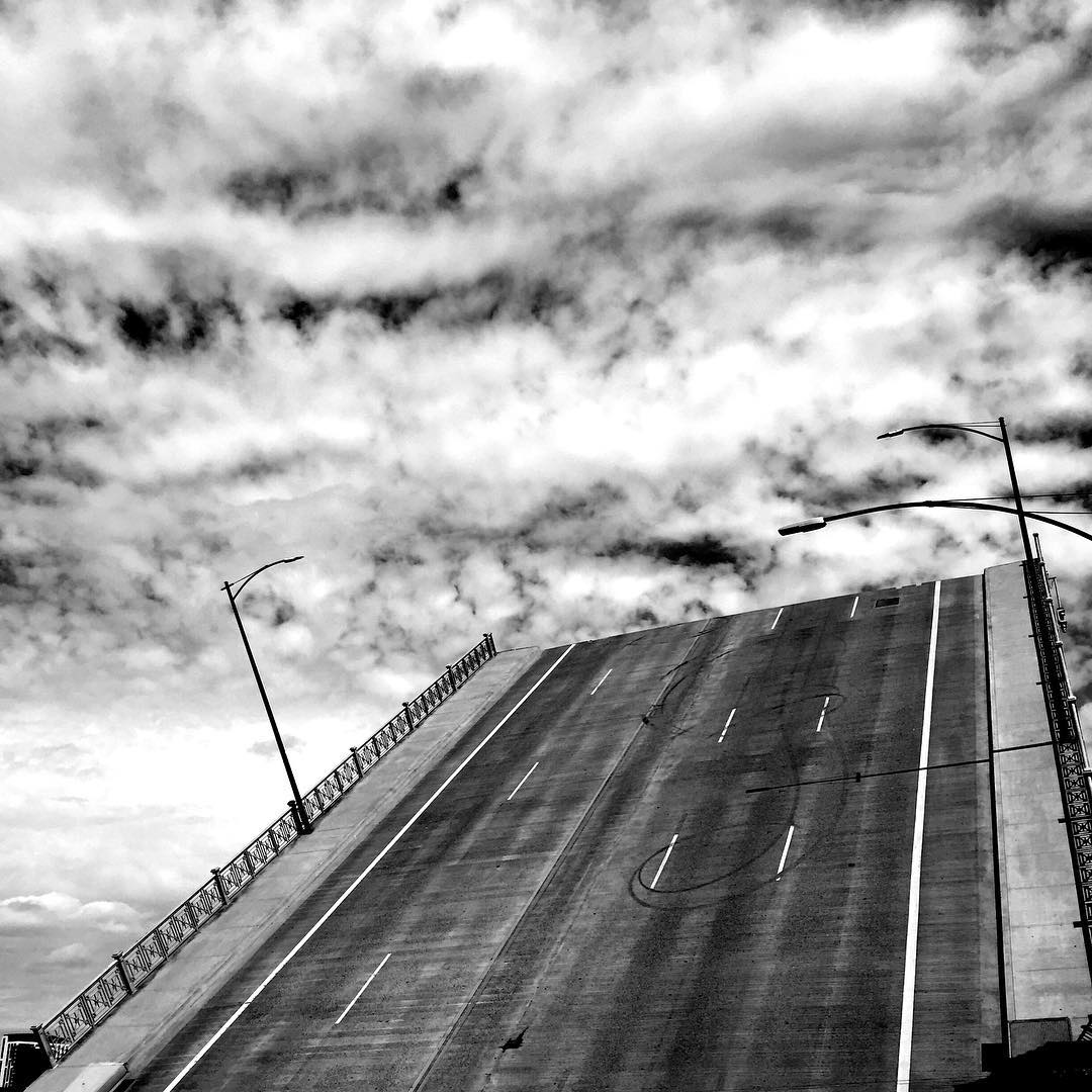 a picture of a drawbridge raised against a summer sky