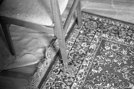 a black and white photograph of a dirty wood floor and rugs and the legs of a midcentury modern dining chair