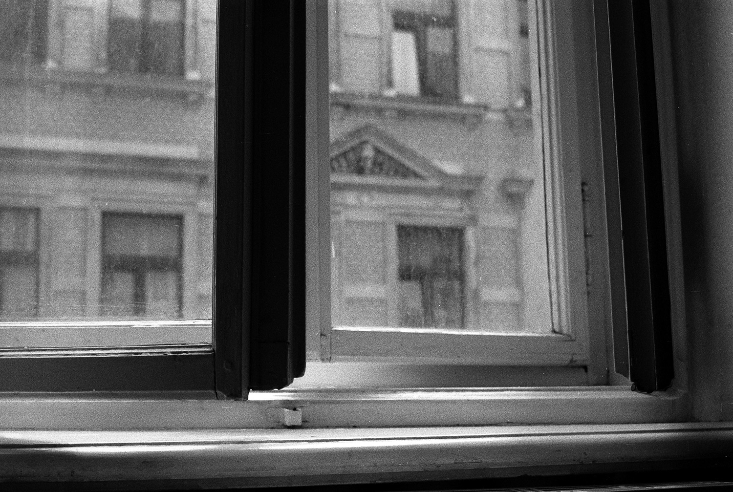 A scan of a photograph on black and white film of a slightly open window.