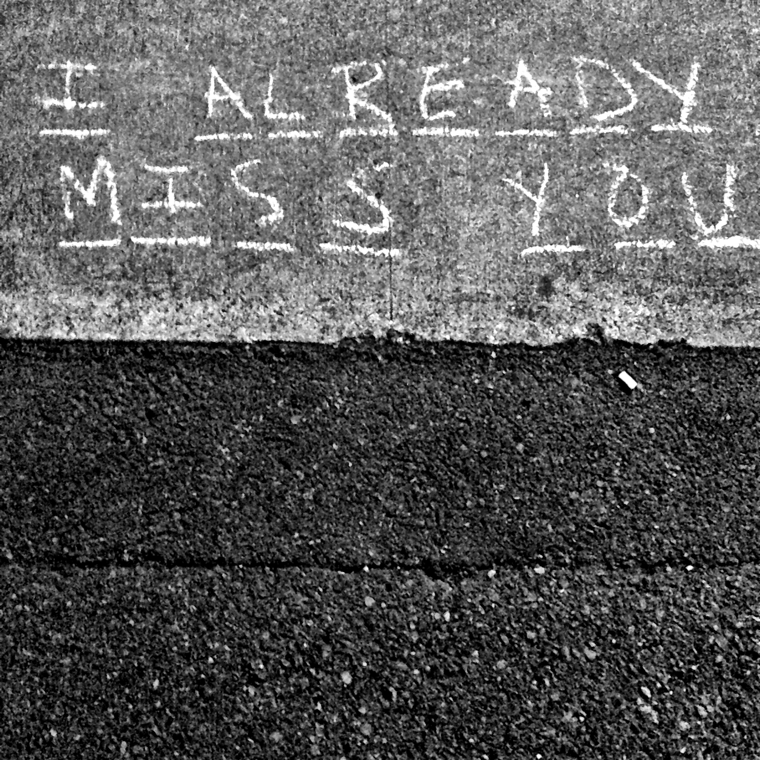 A photograph of a sidewalk on which some words have been written in chalk