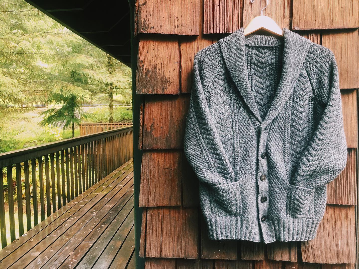 An image of a grey textured cardigan with a shawl collar and sleeves shoved into pockets, hung on a hanger against the cedar shakes on the corner of a cabin. The background is very green and springlike.