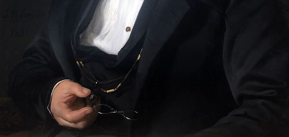 Detail of a painting, showing a hand holding a pair of silver spectacles suspended from a black cord against a background of black fabric, presumably a coat.