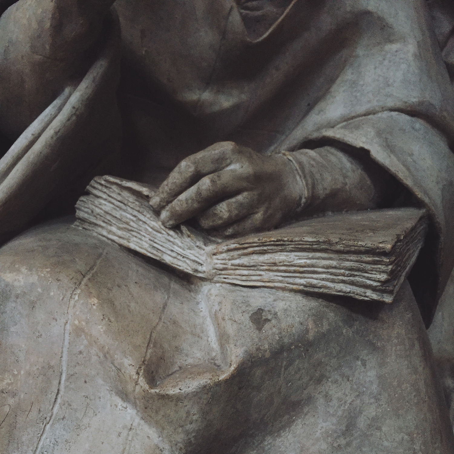 Sculpture of a book in the lap of probably a saint, but it's not quite clear